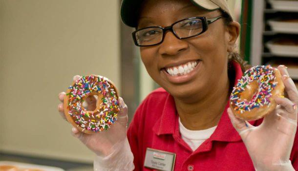 Holding 2 Rainbow Sprinkle Donuts